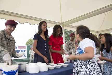 First Lady Michelle Obama and Malia Obama help serve ice cream to military families