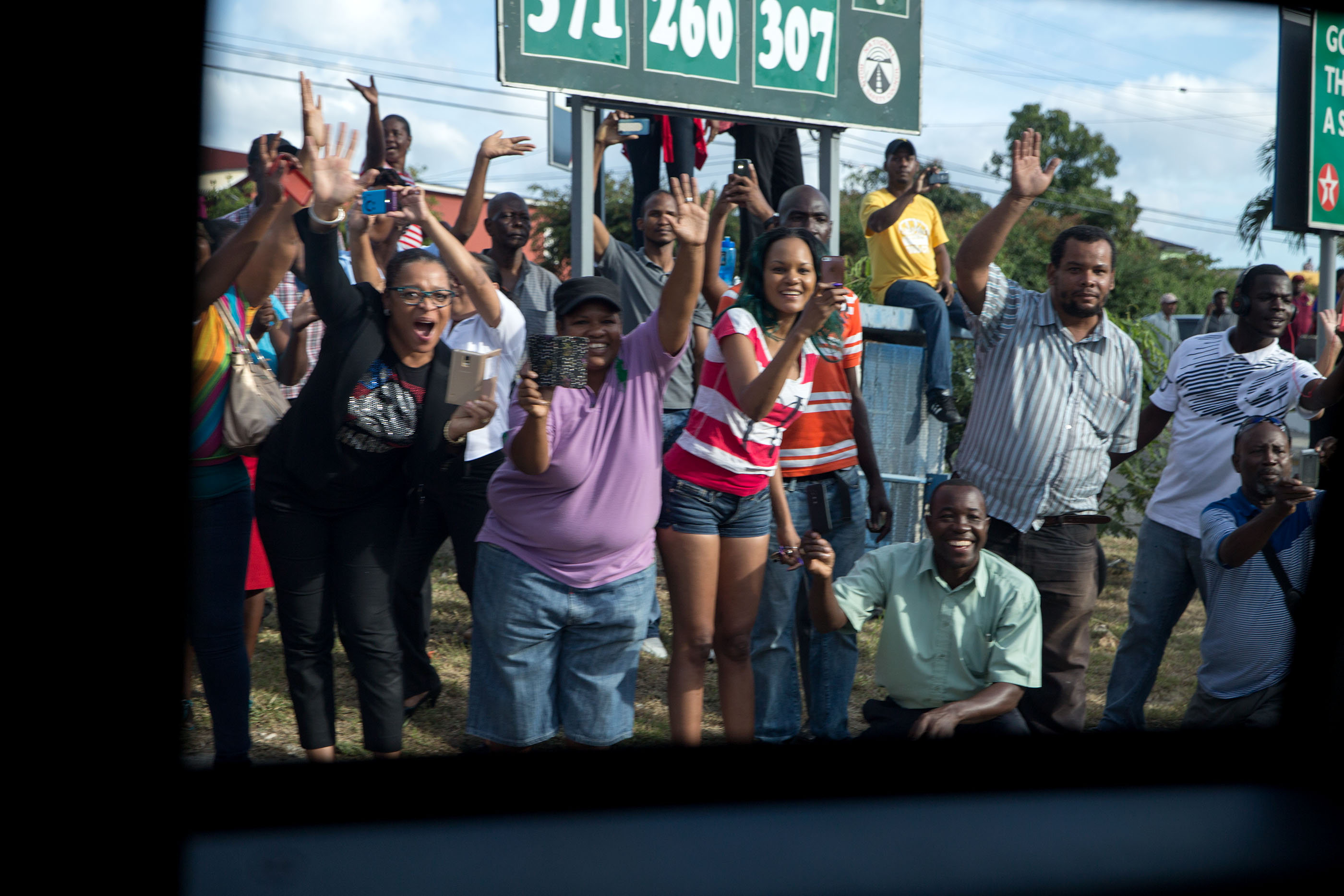 Jamaicans wave at the passing motorcade. (Official White House Photo by Pete Souza)