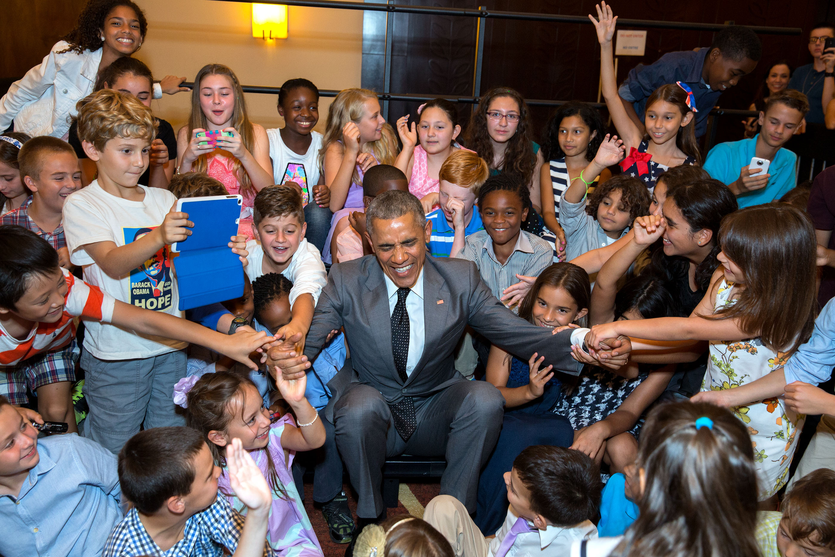 Children of U.S. Embassy personnel help President Obama to his feet after he posed for a group photo with them at the Westin Playa Bonita hotel in Panama City. (Official White House Photo by Pete Souza)