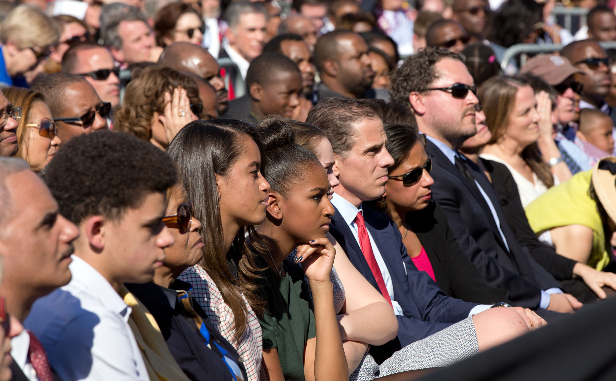 Malia and Sasha Obama and other family, friends, and White House staff listen to the President. Attorney General Eric Holder is at far left. (Official White House Photo by Pete Souza)