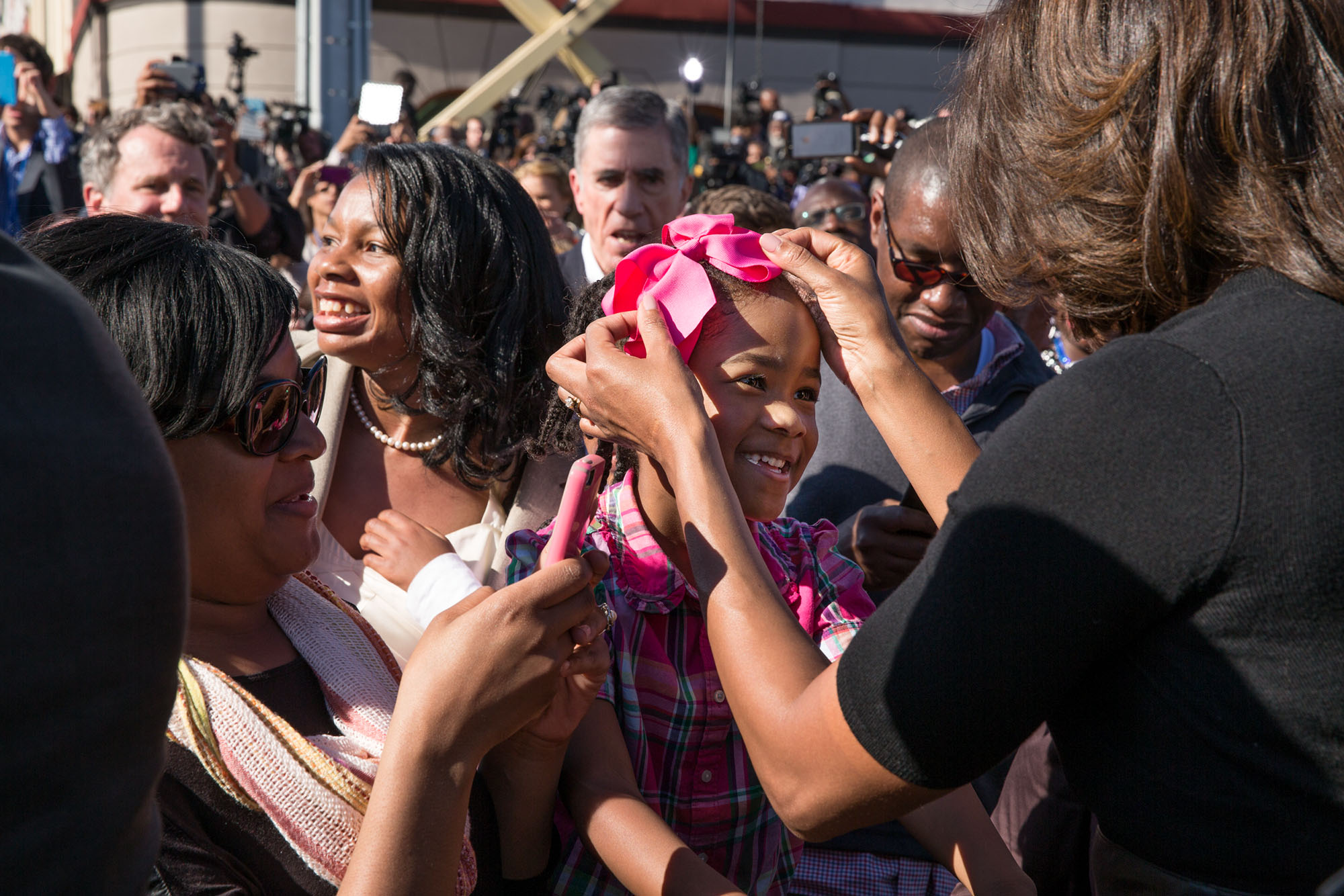 First Lady Michelle Obama adjusts the bow in the hair of a young girl. (Official White House Photo by Pete Souza)
