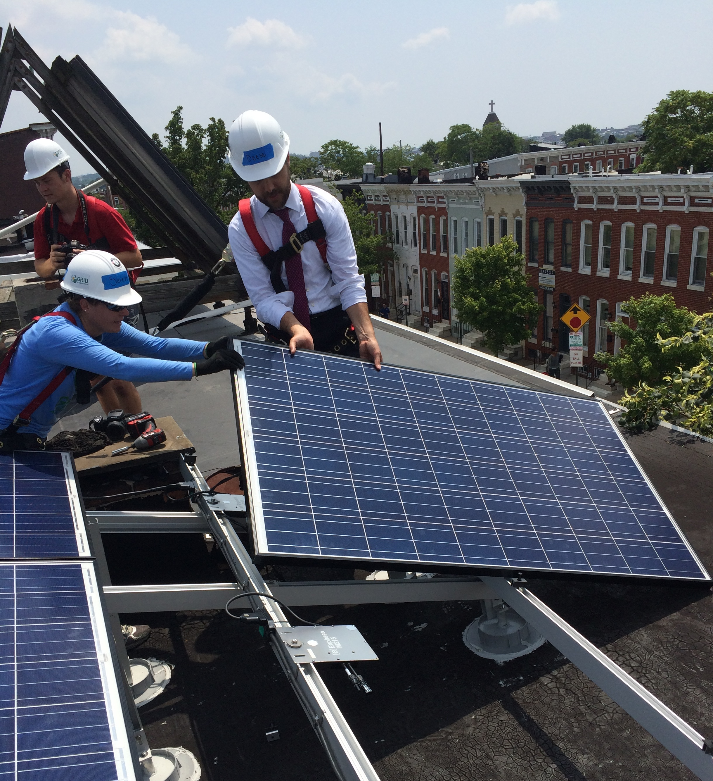 Senior Advisor to the President Brian Deese installing solar panels on a roof in Baltimore