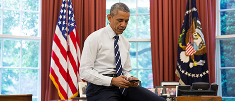 President Obama sitting on his desk in The Oval Office tweeting