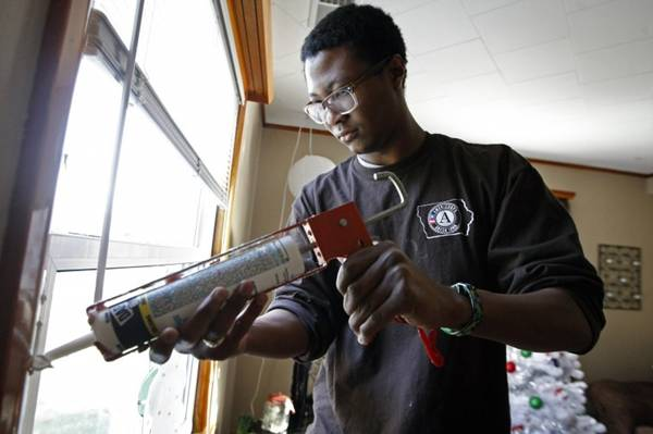 Brandon Gibbs, a Green Iowa AmeriCorps member, caulks the edges of a window frame in a home he is weatherizing in Dubuque, Iowa.