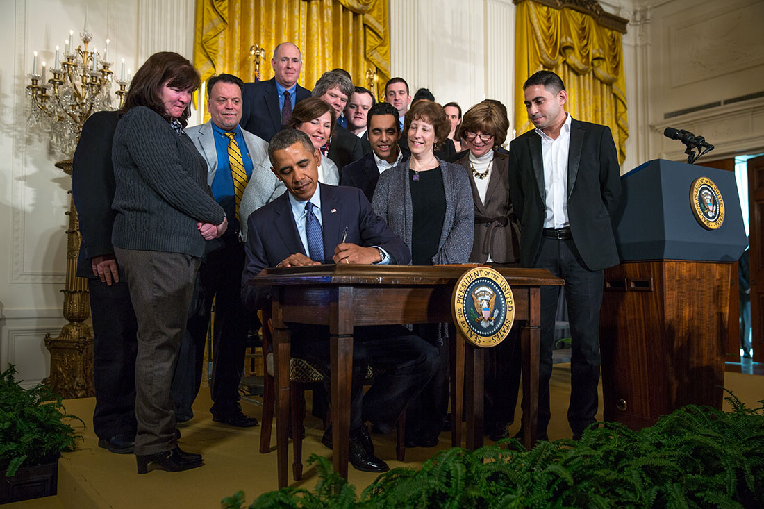 President Barack Obama signs a Presidential Memorandum on updating the overtime pay system, in the East Room of the White House, March 13, 2014.