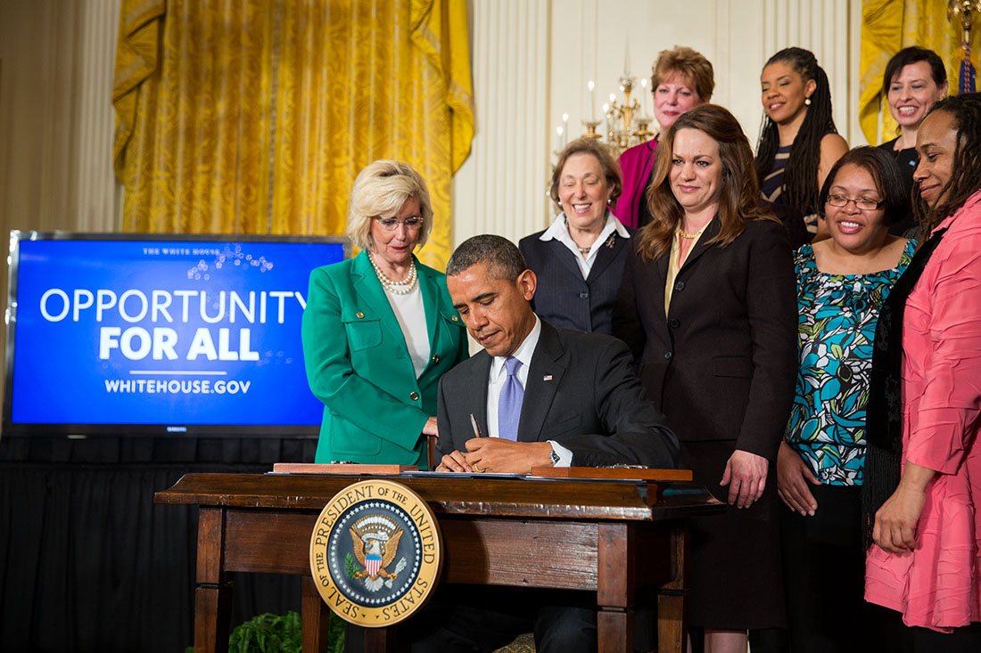President Barack Obama signs executive actions to strengthen enforcement of equal pay laws for women, at an event marking Equal Pay Day, in the East Room of the White House, April 8, 2014.