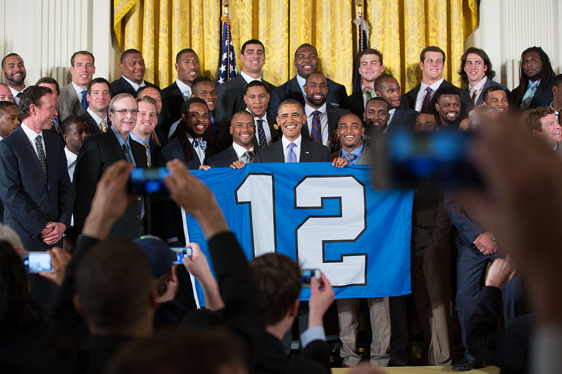 President Barack Obama holds a 12th man flag with the Super Bowl Champion Seattle Seahawks during an event to honor the team and their Super Bowl XLVIII victory