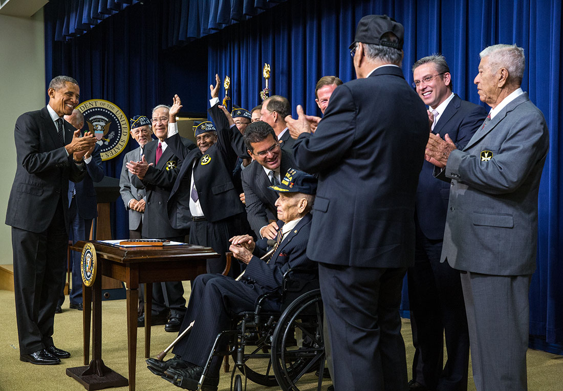President Barack Obama leads an ovation for the Borinqueneers after he signed H.R. 1726