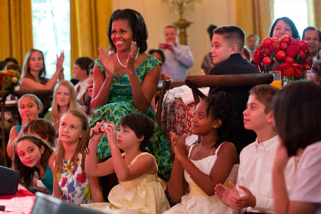 First Lady Michelle Obama and guests applaud as Big Time Rush performs during the Kids' State Dinner