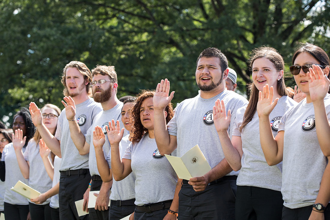 Volunteers take the AmeriCorps pledge during an event to honor the 20th anniversary of the AmeriCorps national service program