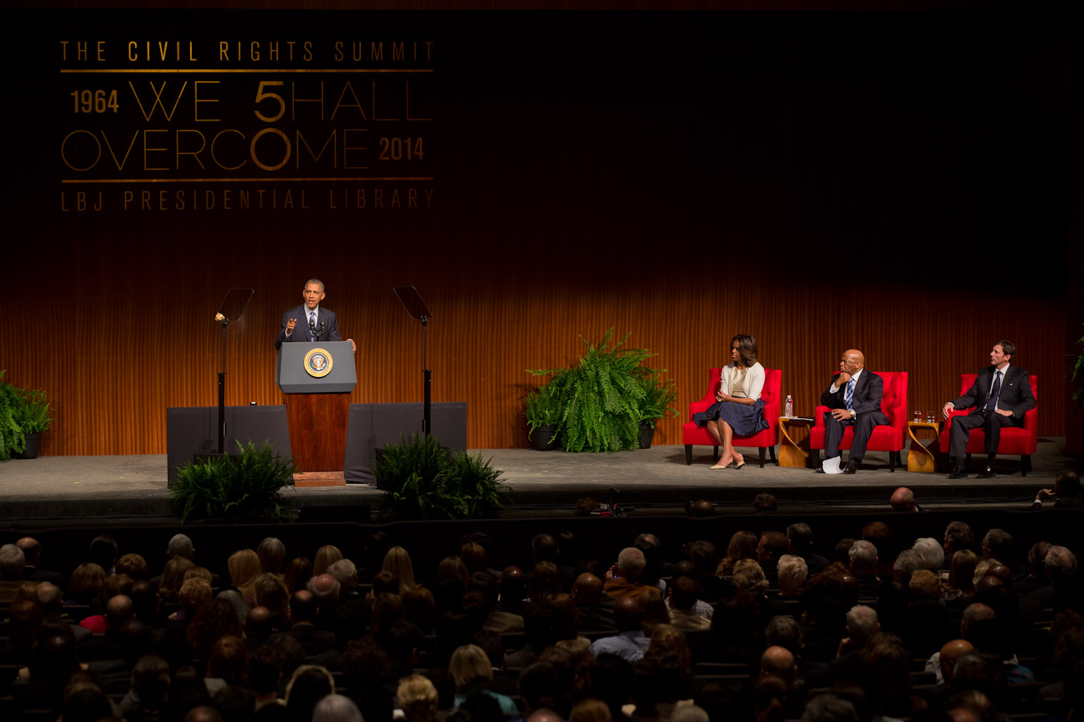 President Barack Obama delivers remarks as First Lady Michelle Obama, Rep. John Lewis, D-Ga., and LBJ Presidential Library Director Mark Updegrove, listen at right at the LBJ Presidential Library
