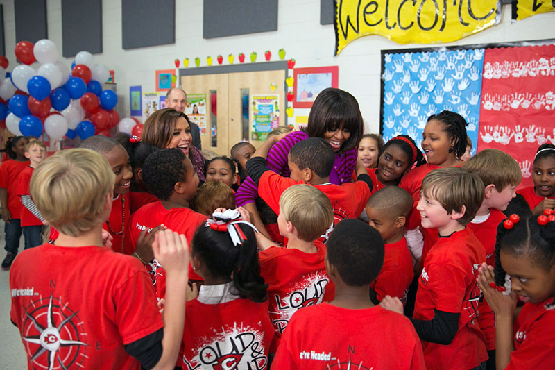 First Lady Michelle Obama and Rachael Ray hug students on the Let's Move 3rd Anniversary Tour