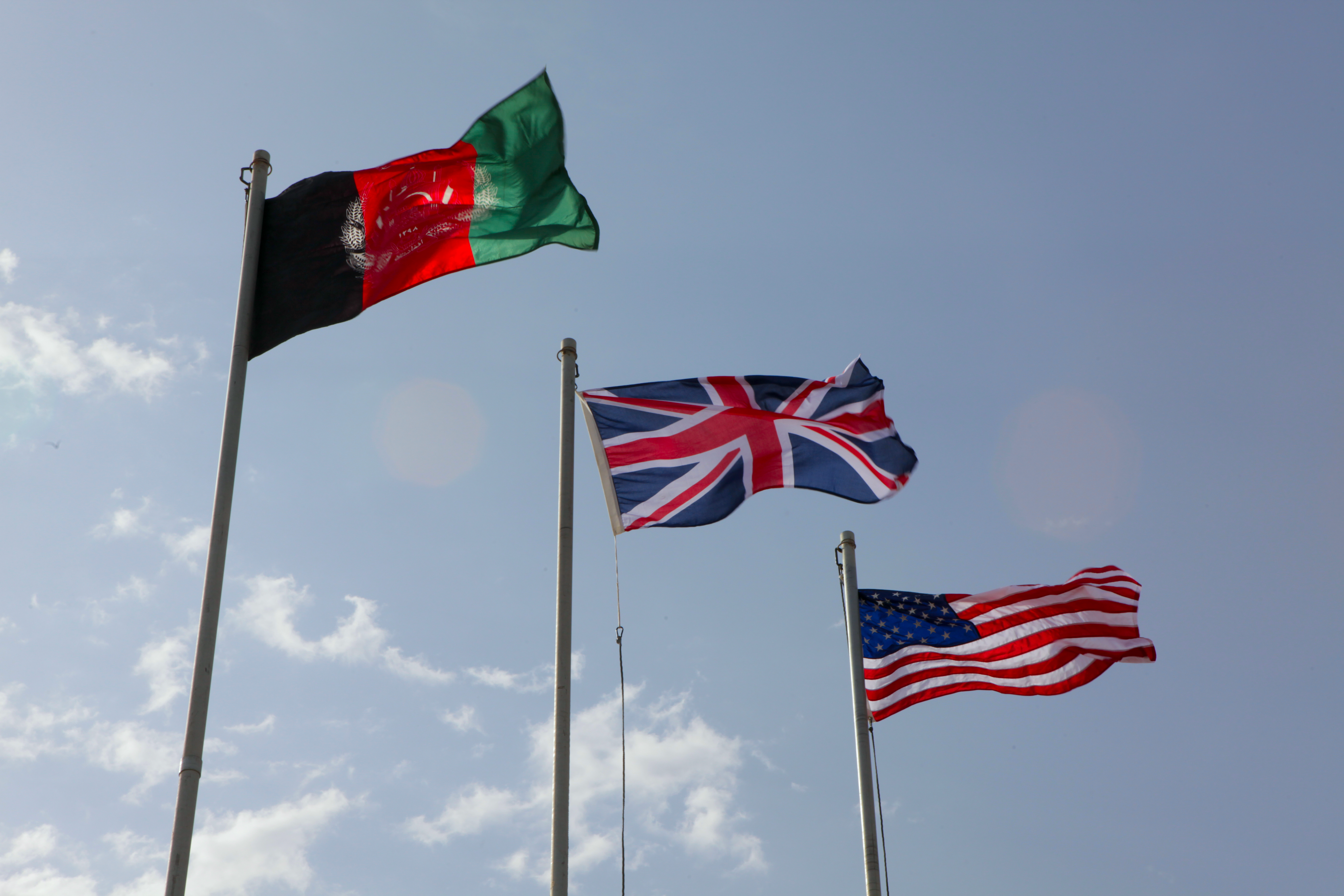 The Union Flag of the United Kingdom waves in the Afghanistan breeze between the Afghanistan and United States flags (March 13, 2012)
