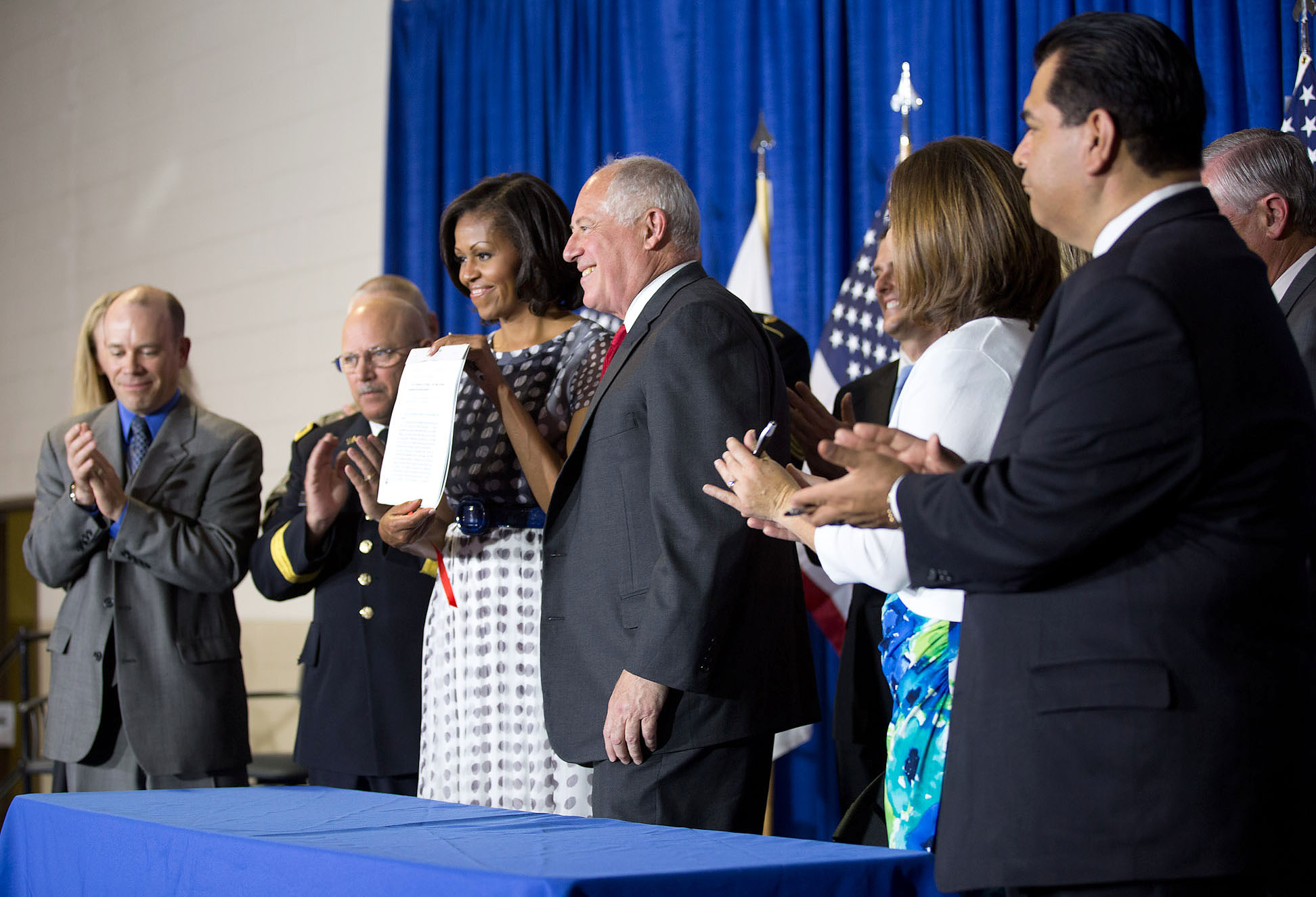 "First Lady Michelle Obama holds the ""Military Family Licensing Act,"" signed by Illinois Gov. Pat Quinn (June 26, 2012)"