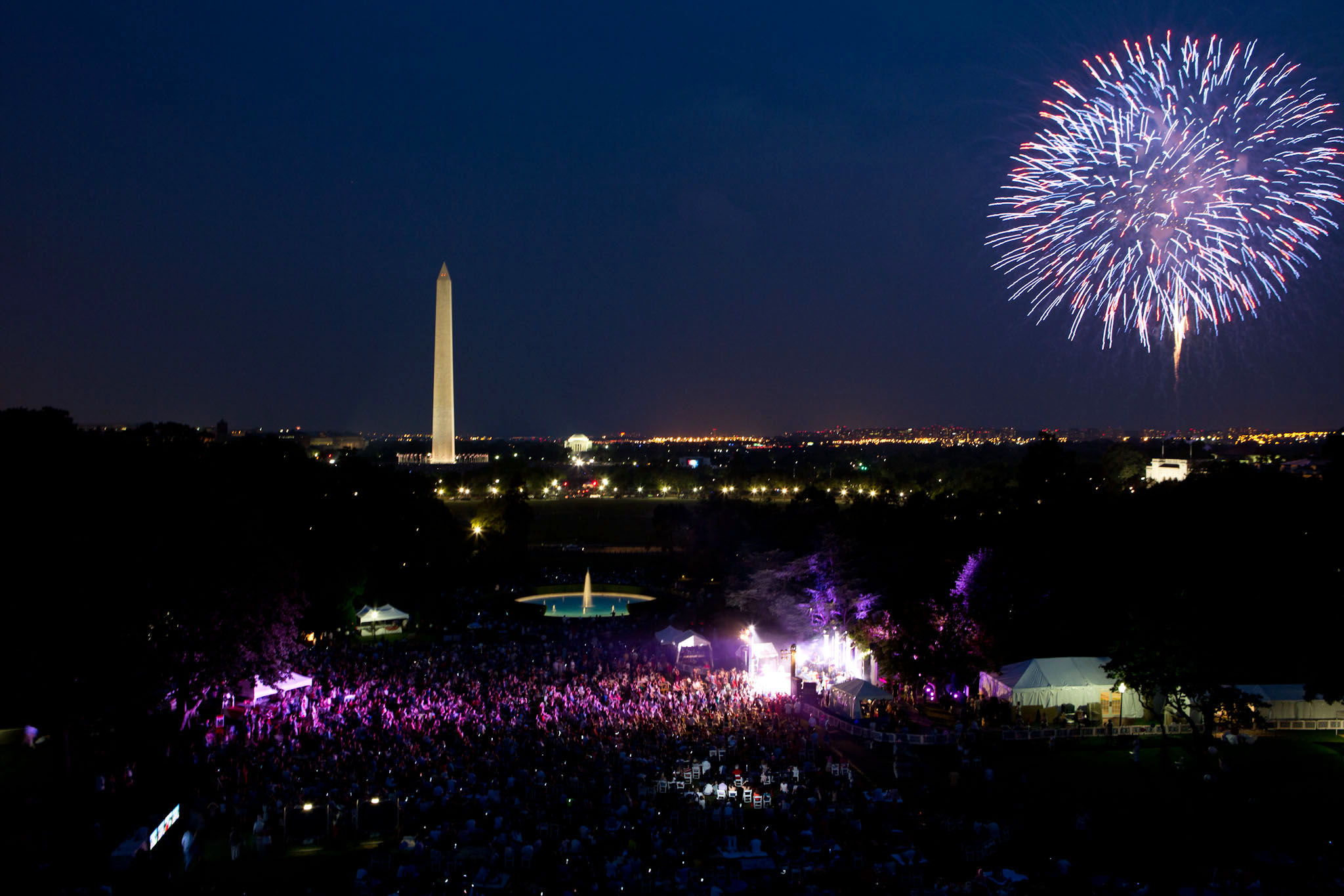 A crowd watches as fireworks erupt over the National Mall (July 4, 2012)