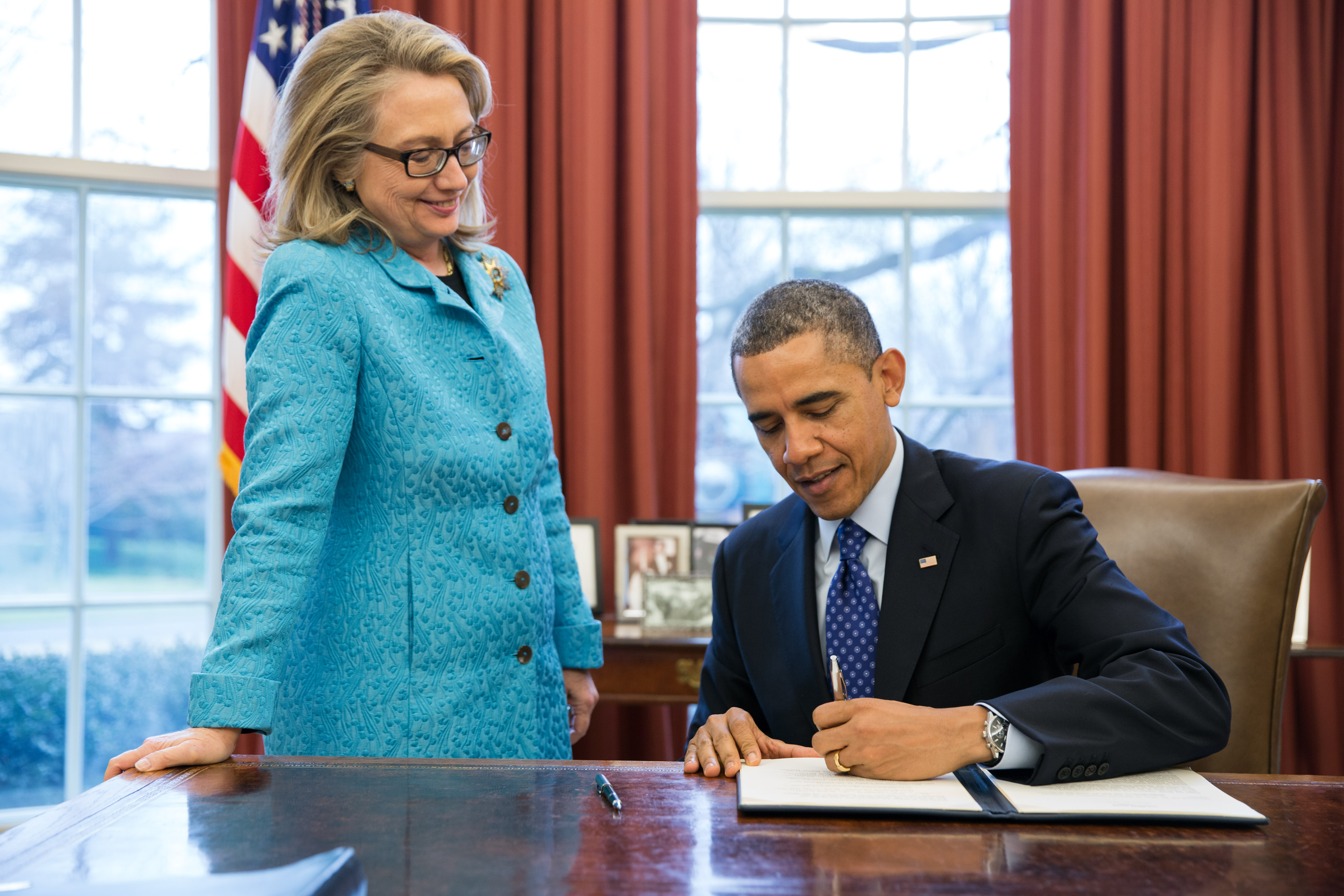 Secretary of State Hillary Clinton watches as President Obama signs a Presidential memorandum (January 20, 2013)