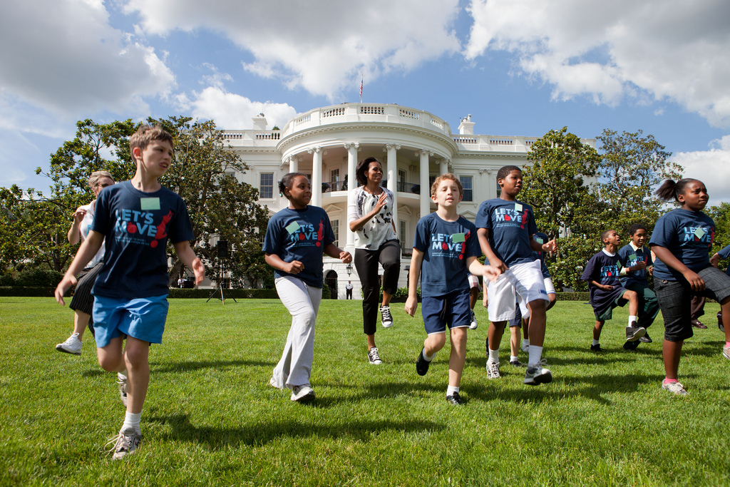 First Lady Michelle Obama runs with kids during the