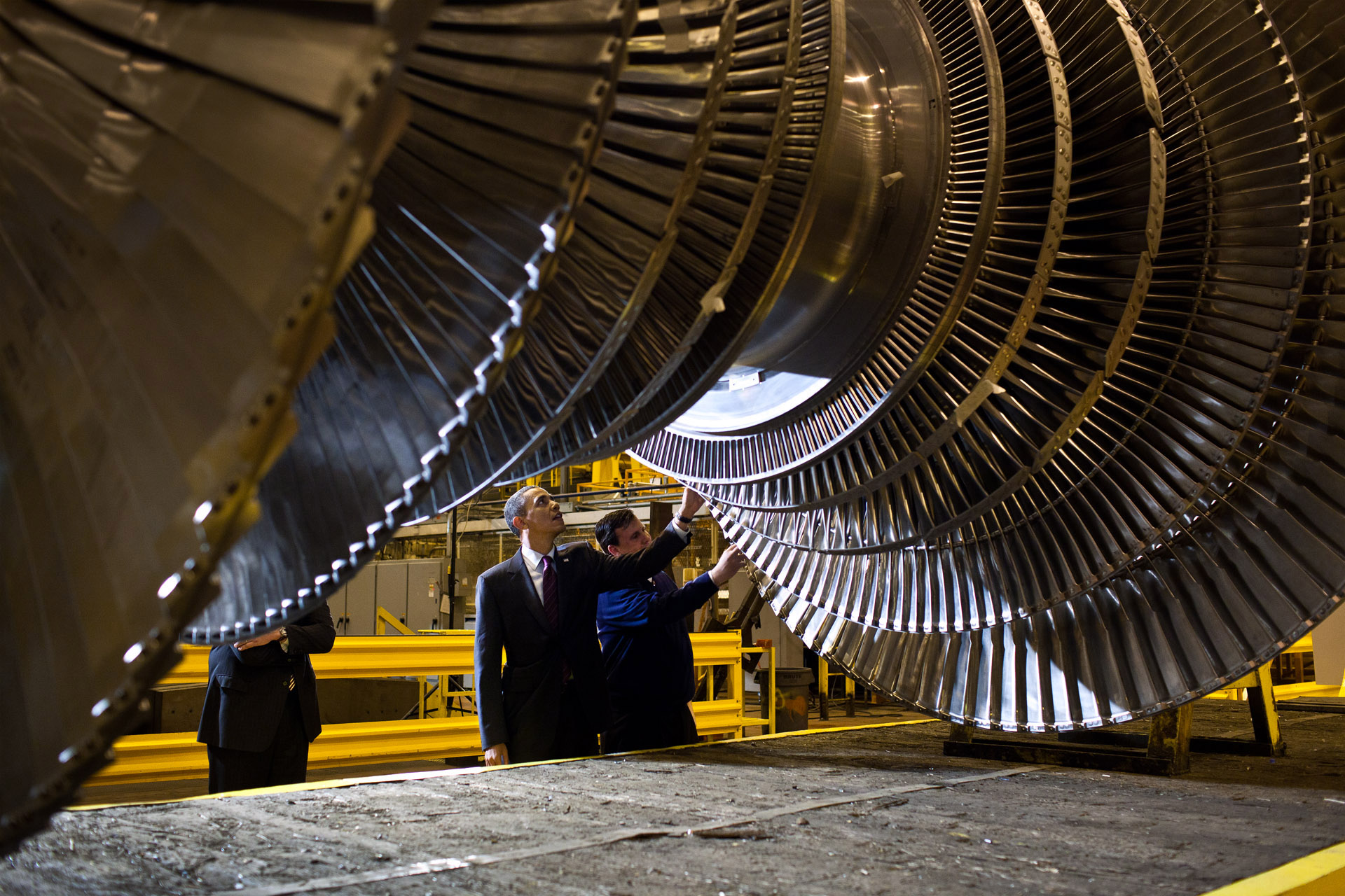 President Barack Obama looks at a turbine rotor while touring the General Electric plant