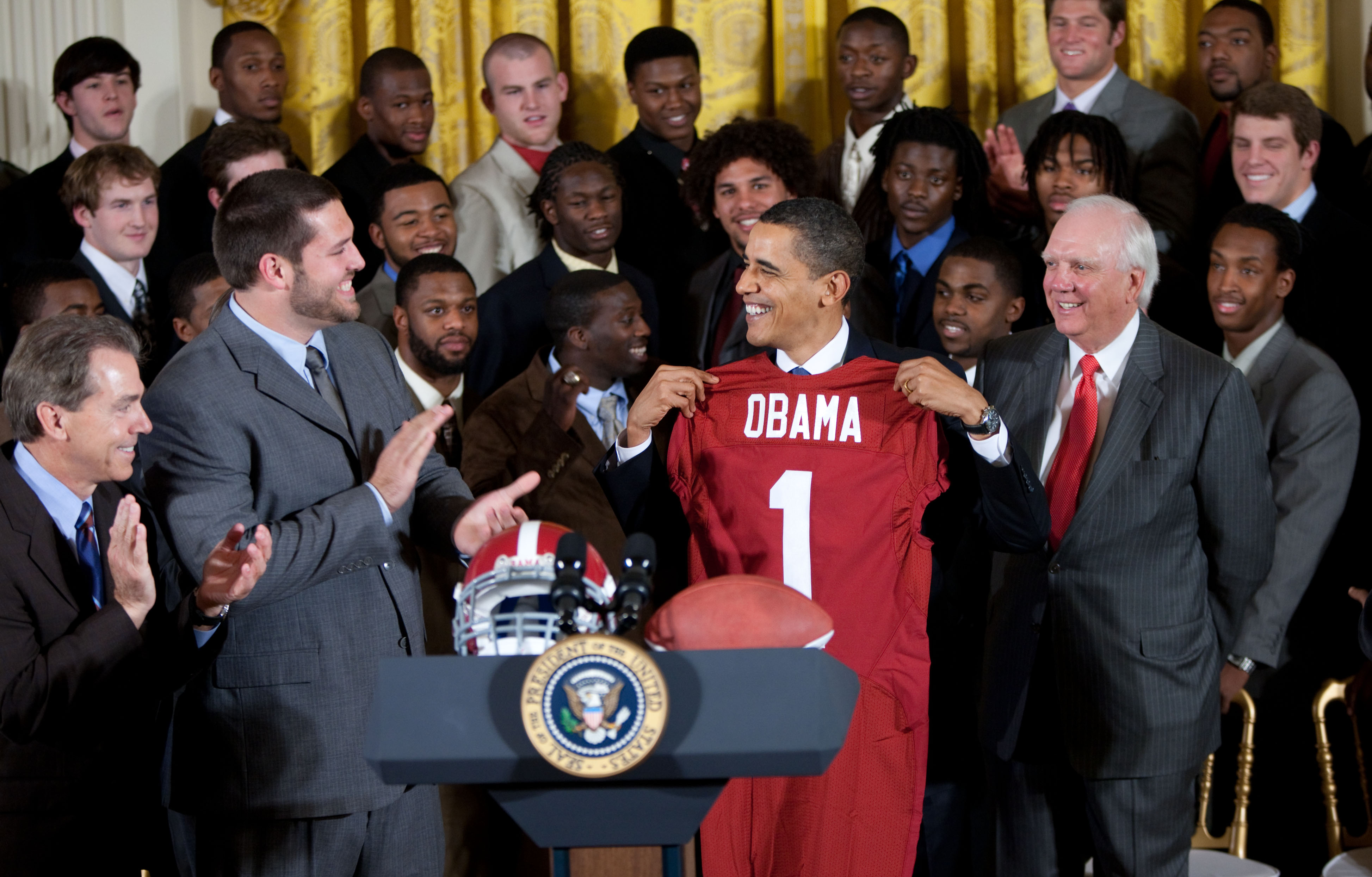 President Barack Obama smiles as he is presented with a University of Alabama football jersey