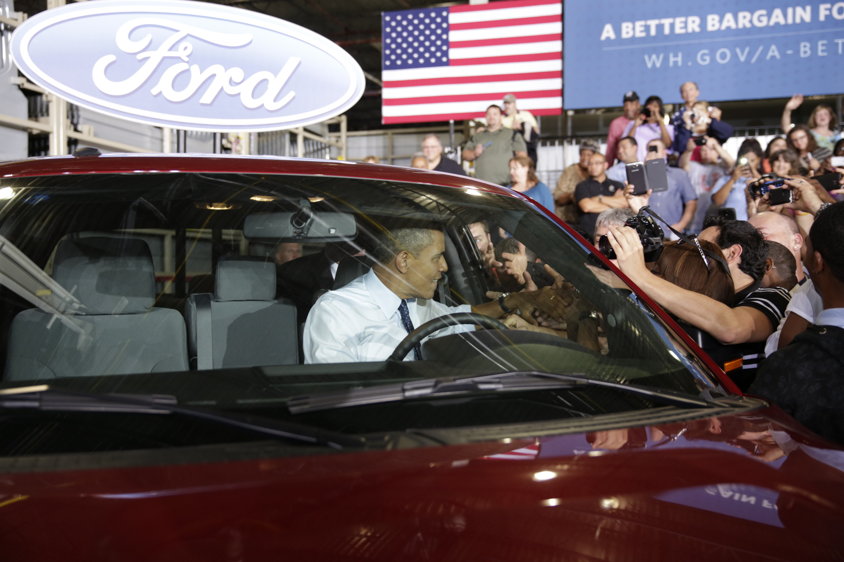 President Barack Obama greets Ford employees from the driver's seat of a Ford truck after delivering remarks on the economy at the Ford Kansas City Stamping Plant