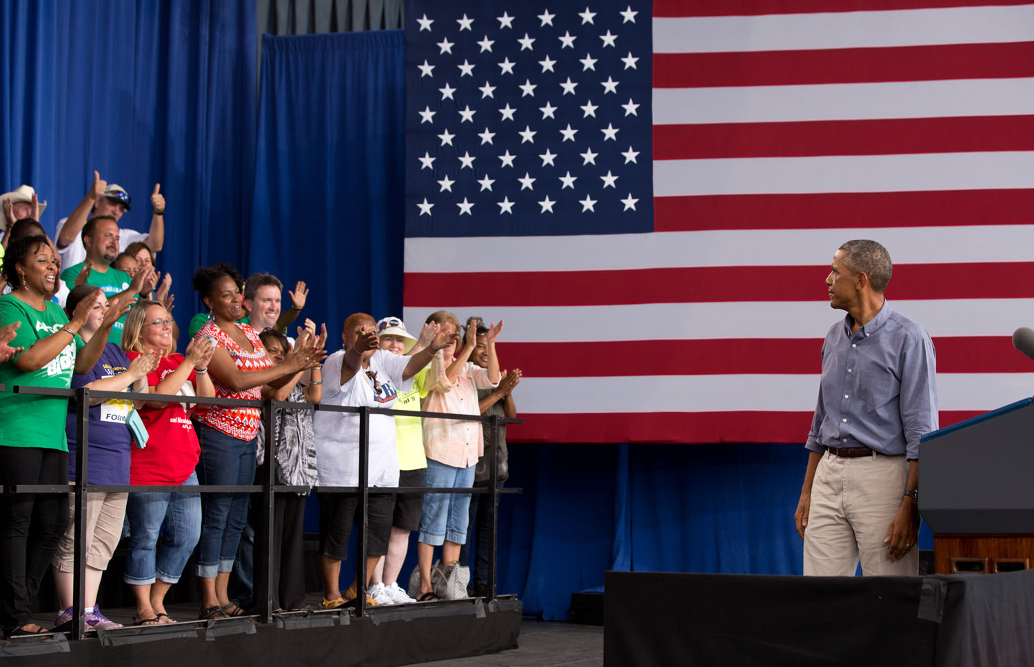 President Barack Obama looks back at the crowd behind him on the stage during remarks at the Milwaukee Laborfest