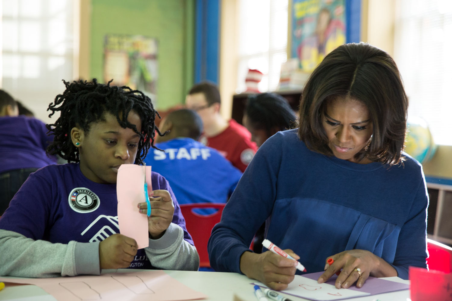 First Lady Michelle Obama works with a young girl during a community service project at the Boys & Girls Club of Greater Washington