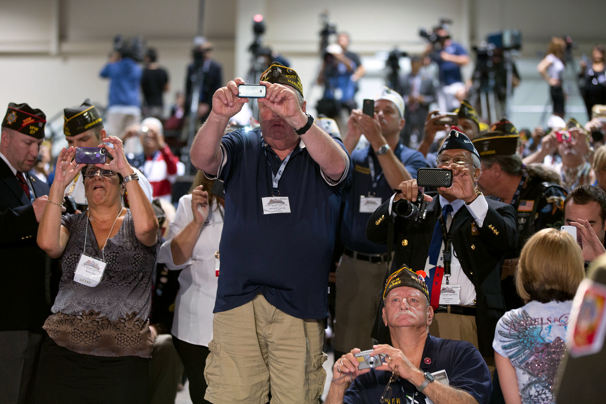 Attendees take photos as President Barack Obama delivers remarks at the 113th National Convention of the Veterans of Foreign Wars
