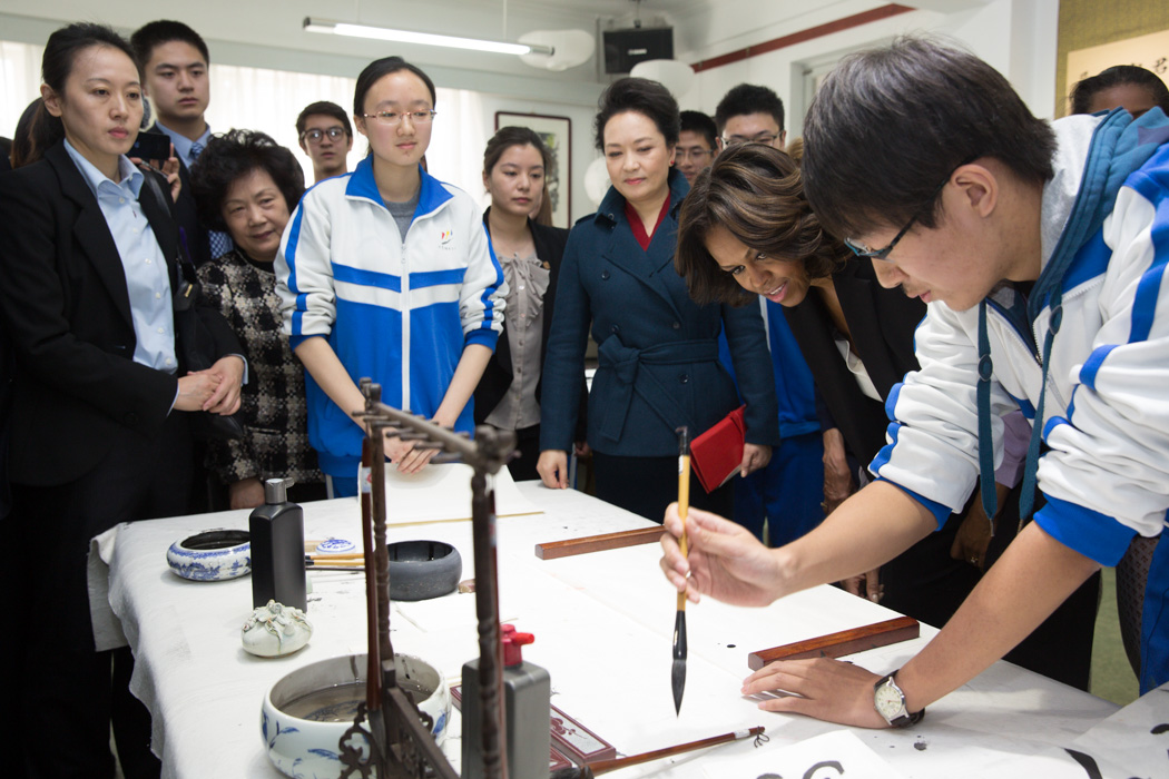 First Lady Michelle Obama visits a calligraphy class with Madam Peng at the Beijing Normal School in Beijing, China