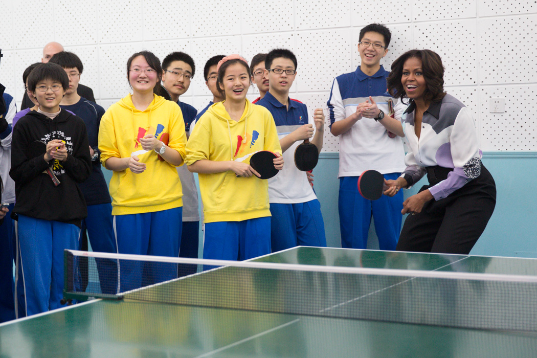 First Lady Michelle Obama plays ping pong with students while touring the Beijing Normal School in Beijing, China