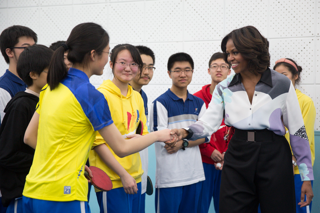 First Lady Michelle Obama greets students after playing ping pong at the Beijing Normal School in Beijing, China