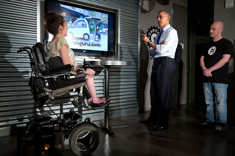 President Barack Obama listens to a presentation about a new car that you can drive a wheelchair into