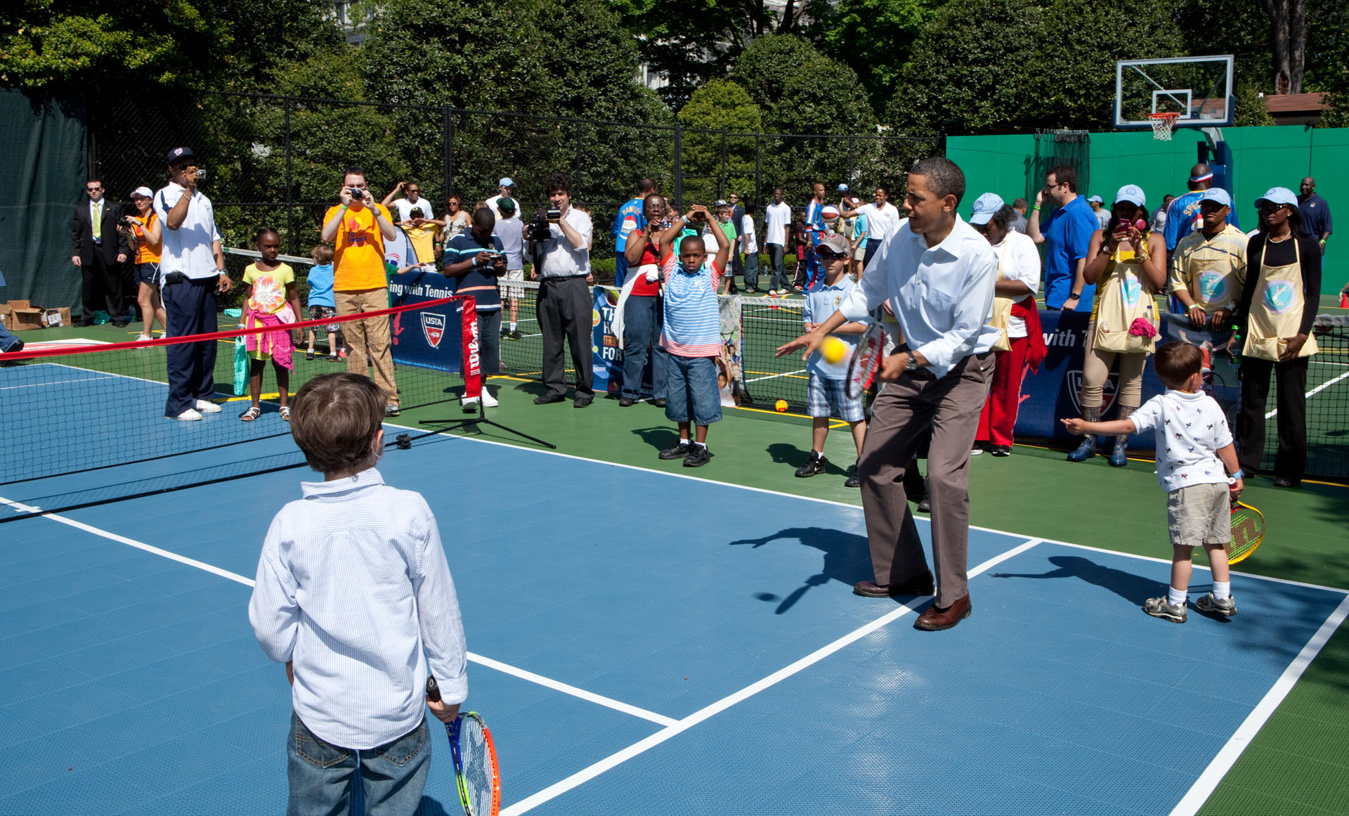 President Barack Obama hits a tennis ball during a sports clinic set up as part of the Easter Egg Roll activities