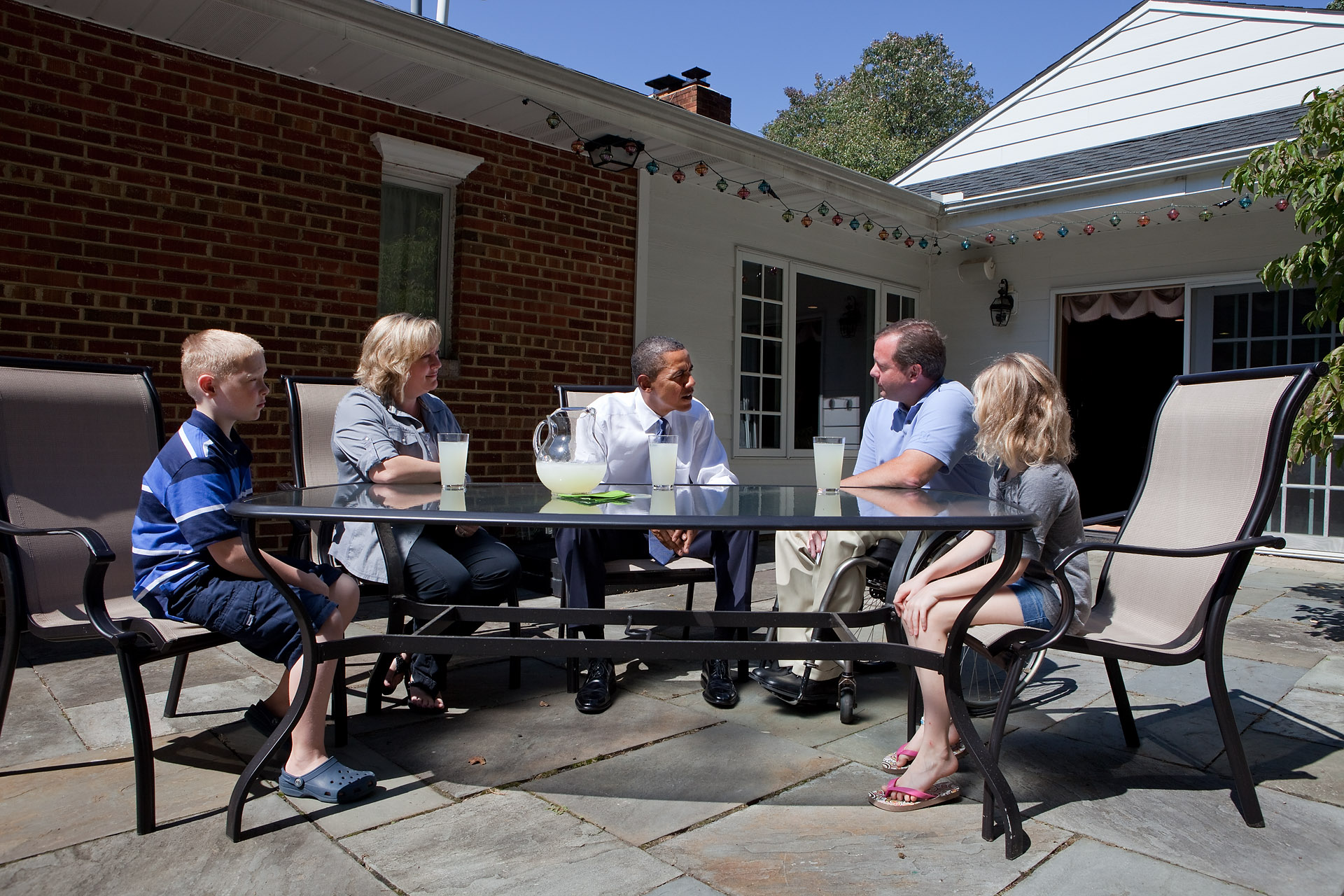 President Barack Obama talks with John Nicholas, Nicole Armstrong, and Their Twins Trevor and Olivia, on the Patio of Their home in Fairfax, Virginia