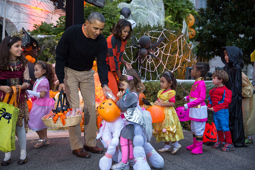 President Barack Obama and First Lady Michelle Obama hand out Halloween treats to local children