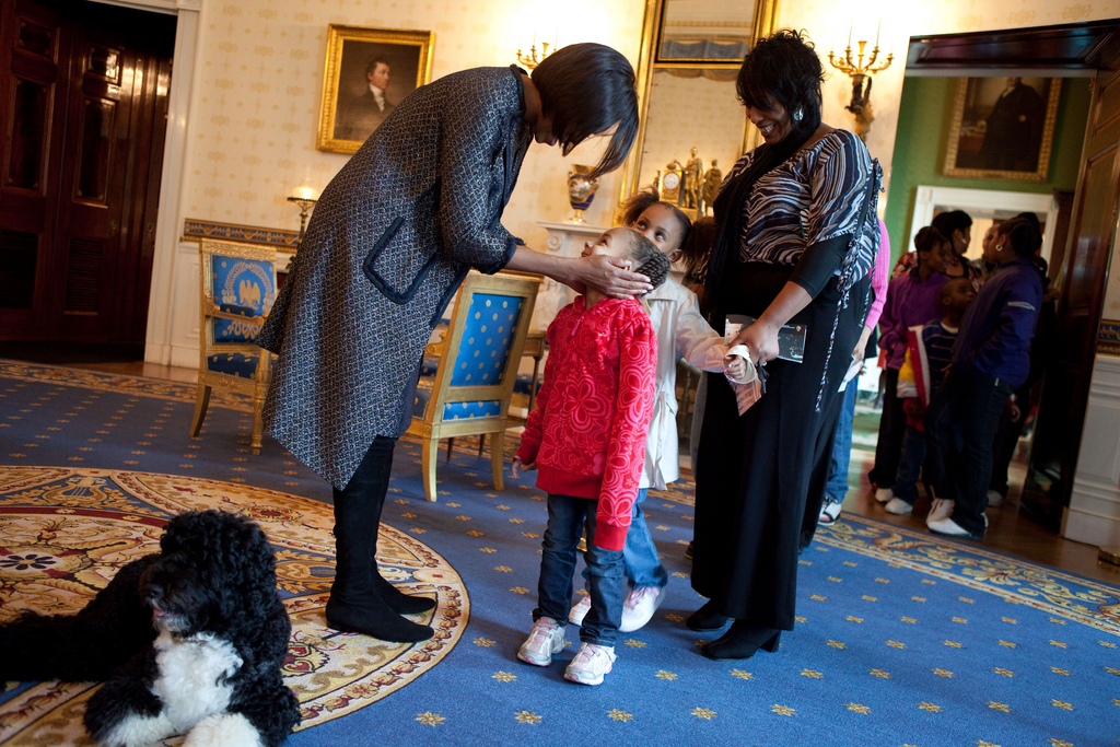 First Lady greets a young visitor touring the White House during a surprise visit in the Blue Room with family dog Bo