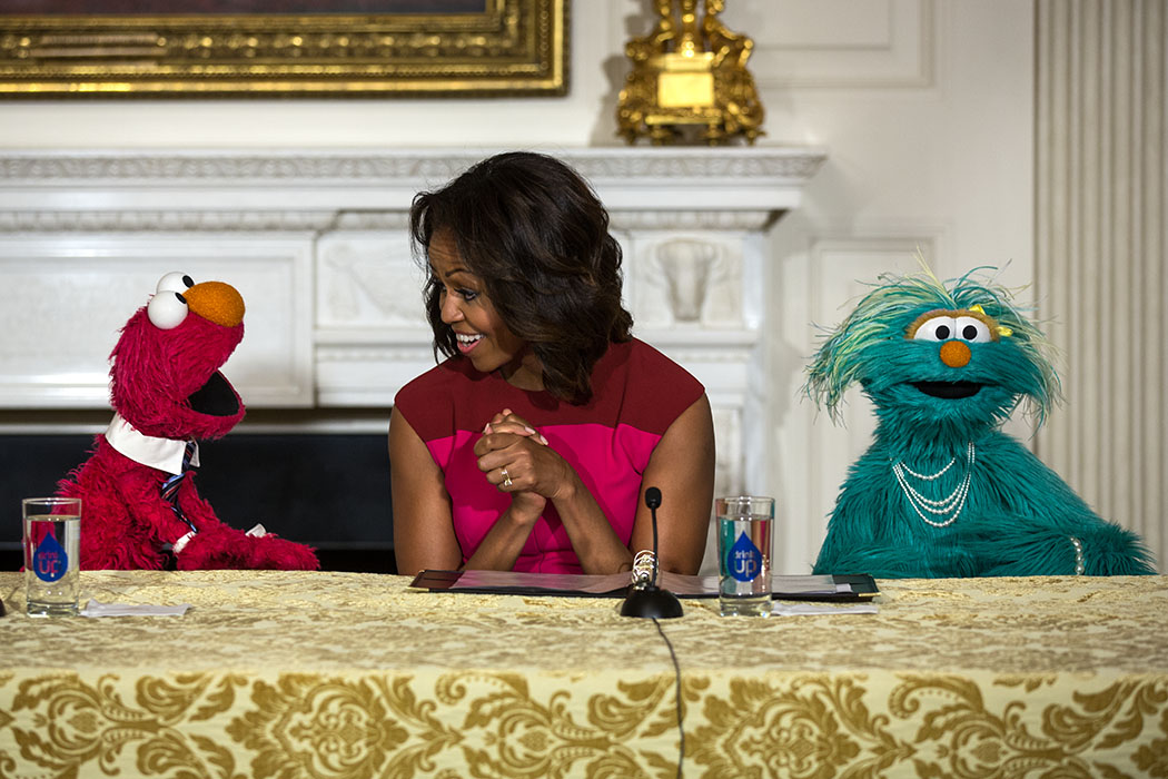 First Lady Michelle Obama, with Sesame Street Muppets Elmo and Rosita, makes a