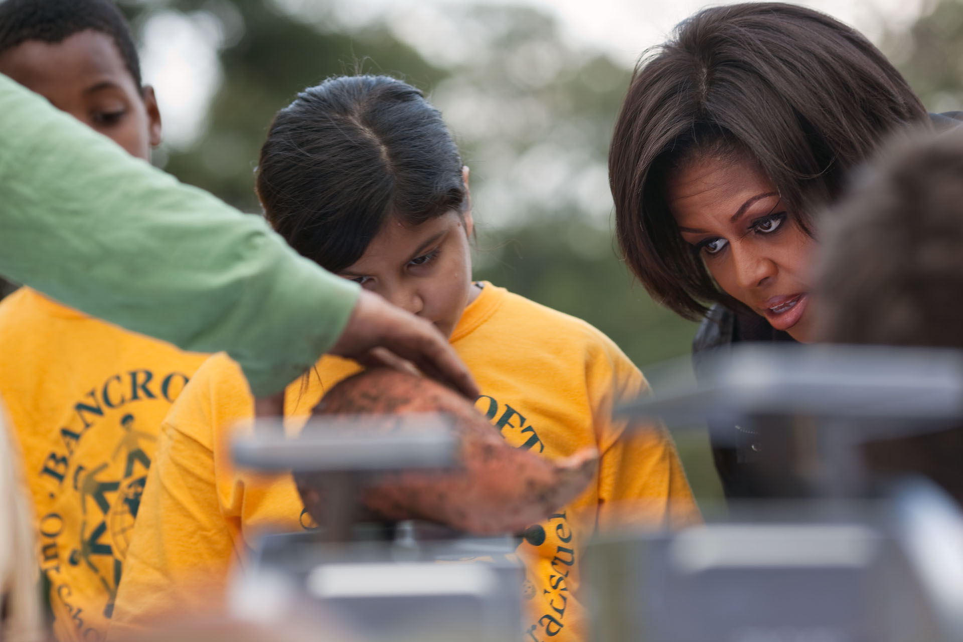 The First Lady and a Young Student Look On as the Harvested Vegetables are Weighed