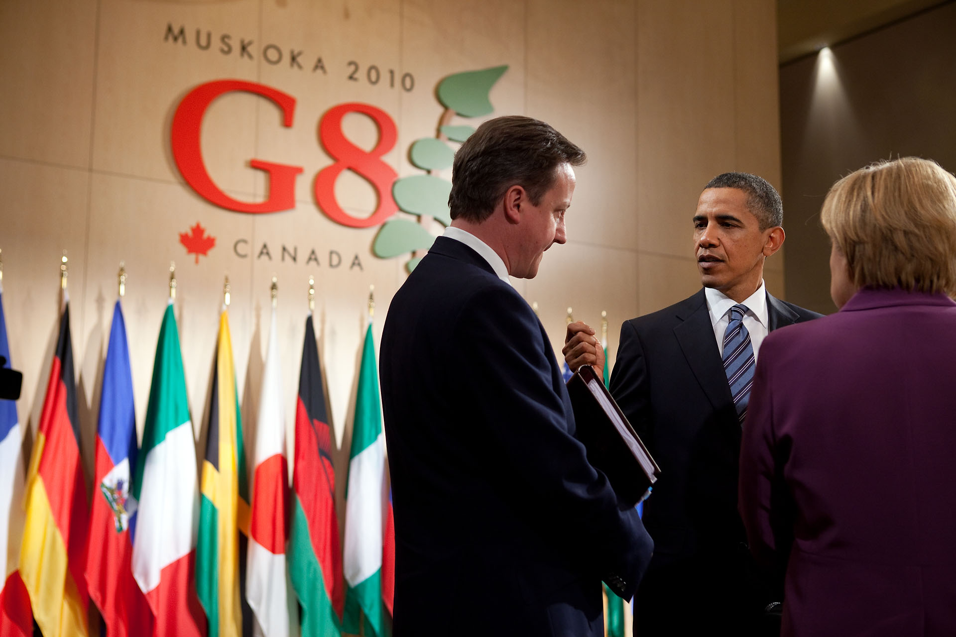 President Barack Obama talks with British Prime Minister David Cameron and German Chancellor Angela Merkel at G8 Summit in Canada