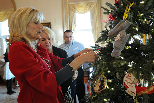 Dr. Biden places an ornament of the National Guard Memorial