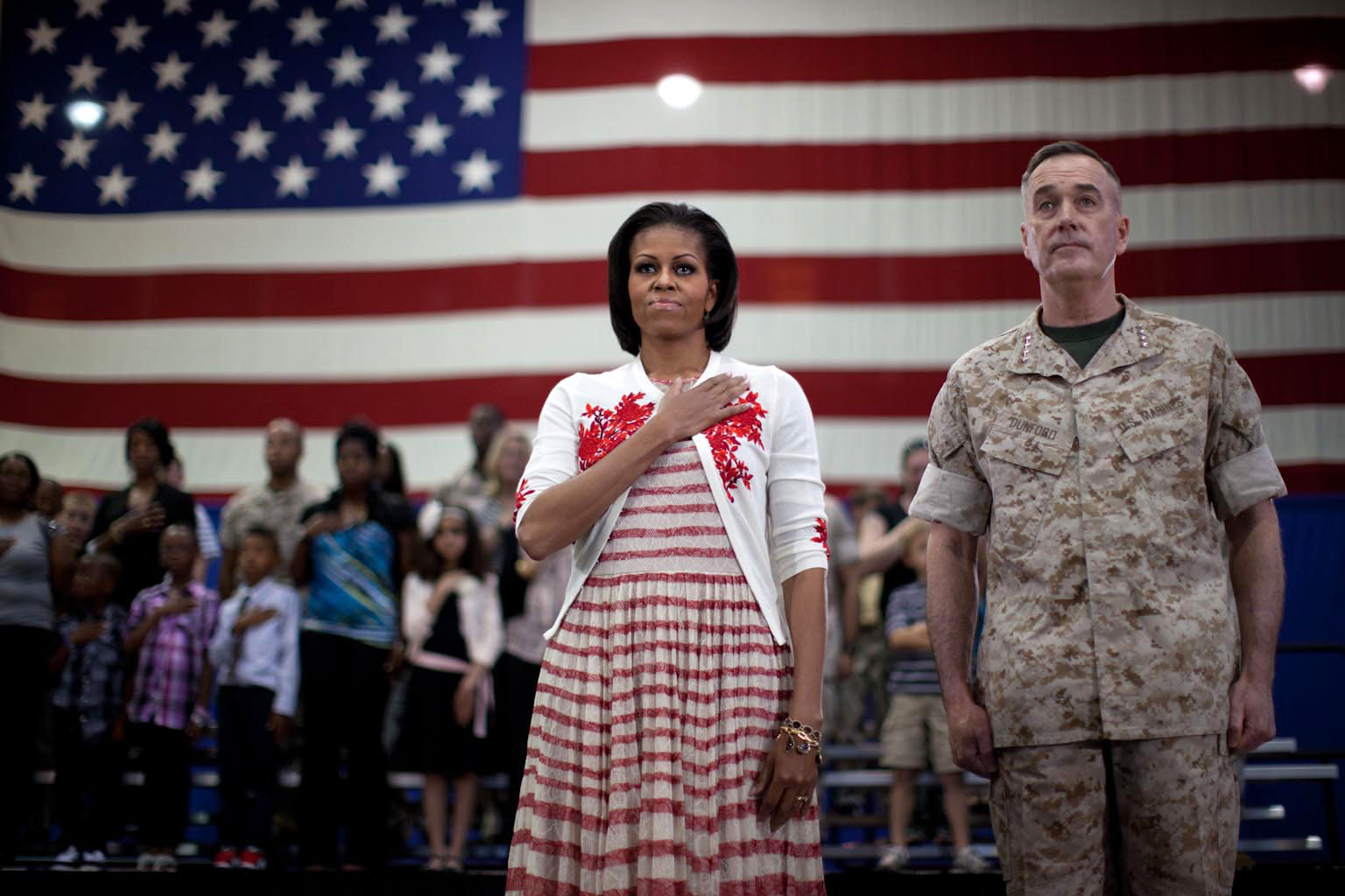 First Lady Michelle Obama and Gen. Joseph Dunford stand during national anthem at Goettge Memorial Field House at Camp Lejeune, N.C.