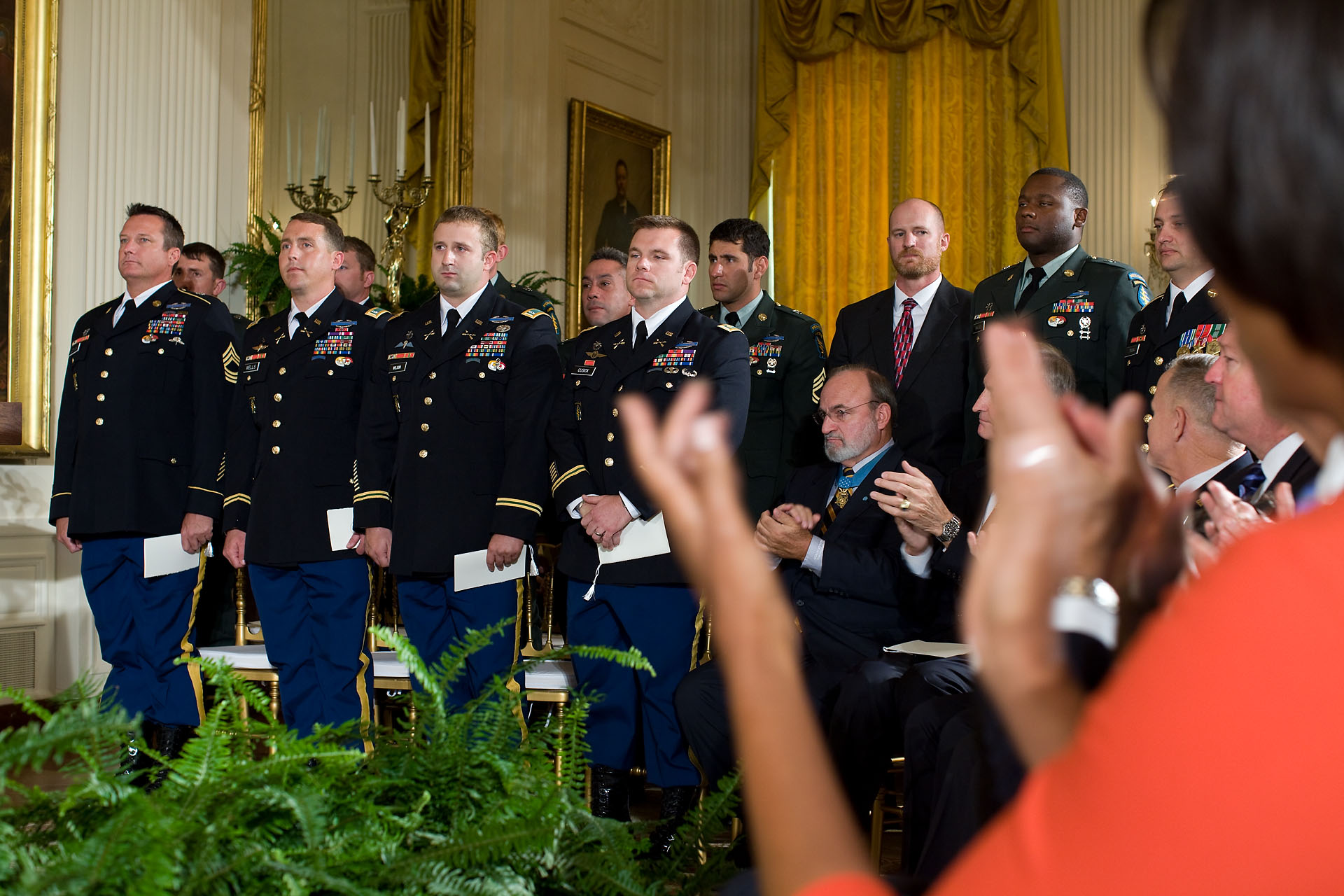 First Lady Michelle Obama Applauds the Members of Staff Sergeant Robert J. Miller's Team Who Were With Him in Afghanistan, During the Presentation of the Medal of Honor