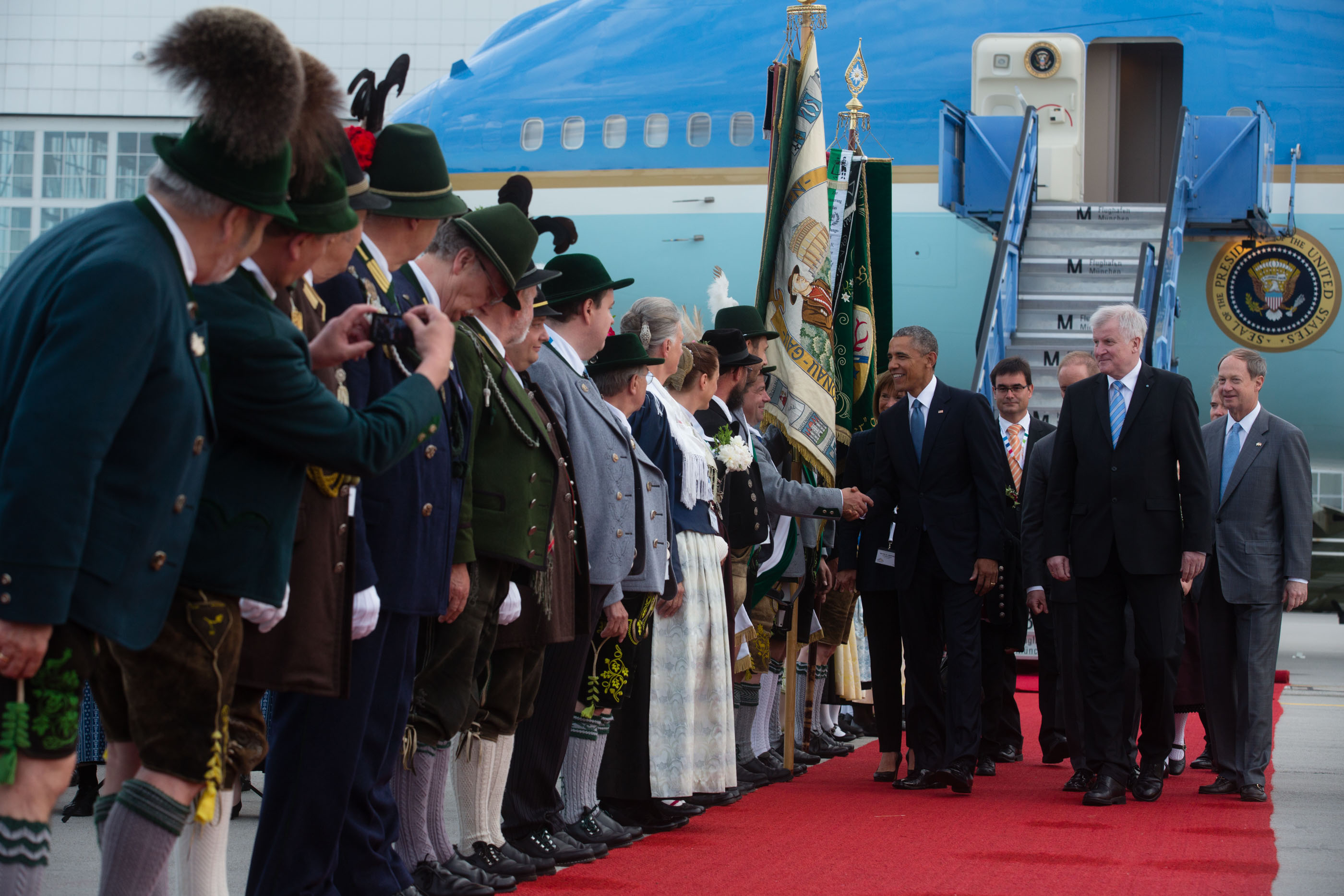 President Obama is greeted by folks in traditional Bavarian dress