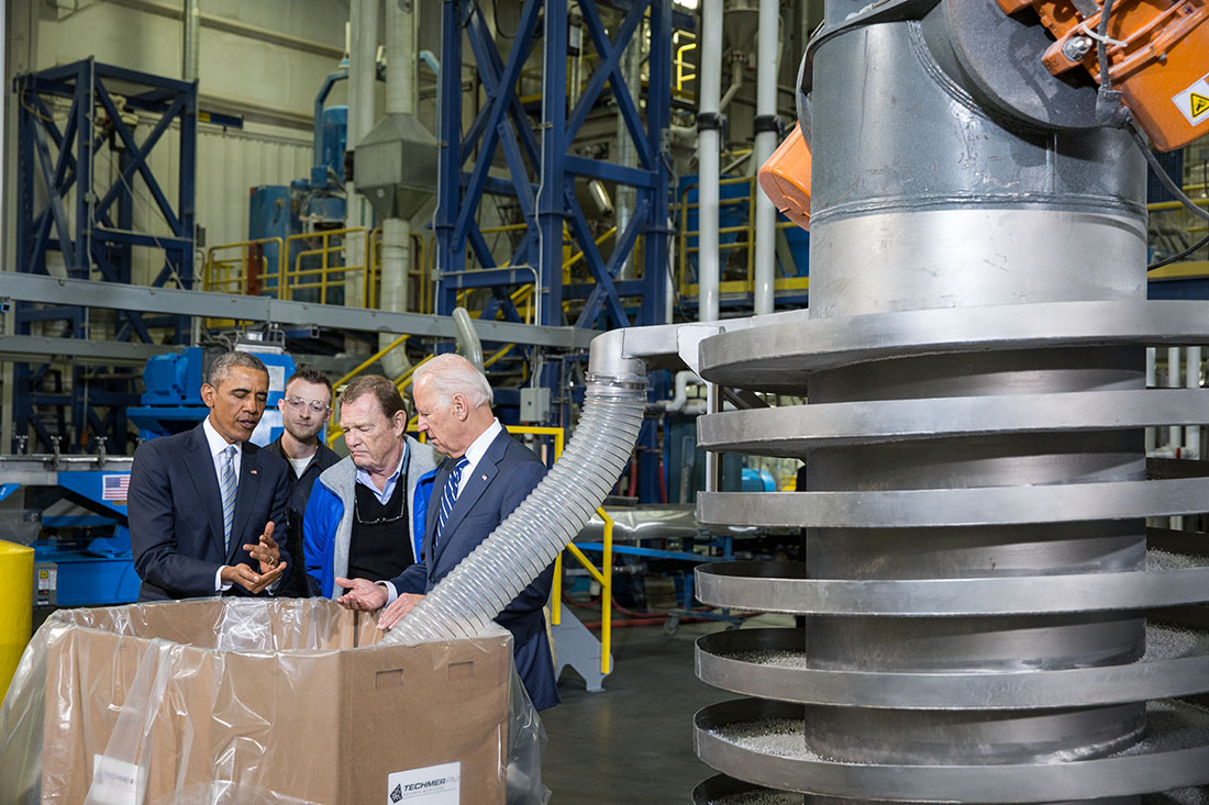 President Obama and Vice President Biden view an extruder machine that combines raw materials to create a specific product, during a tour of Techmer PM