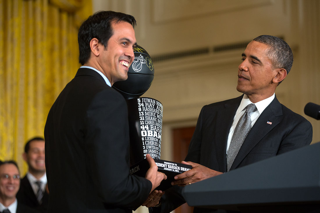 Miami Heat Coach Erik Spoelstra presents President Barack Obama with a team trophy