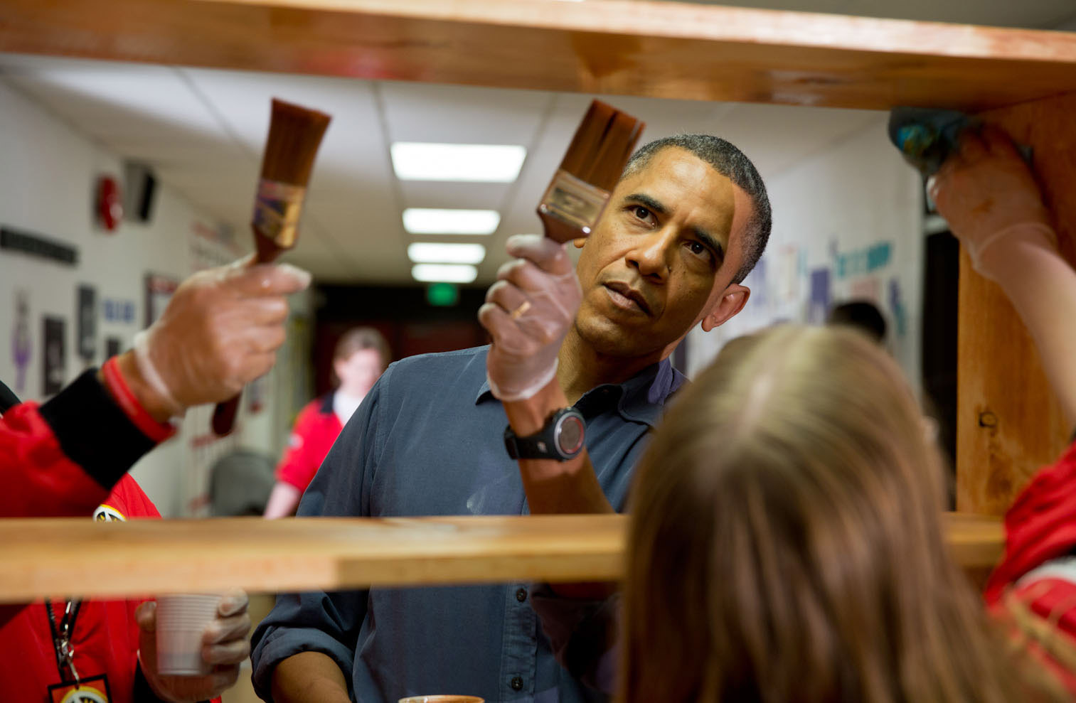 President Barack Obama stains shelves during a National Day of Service