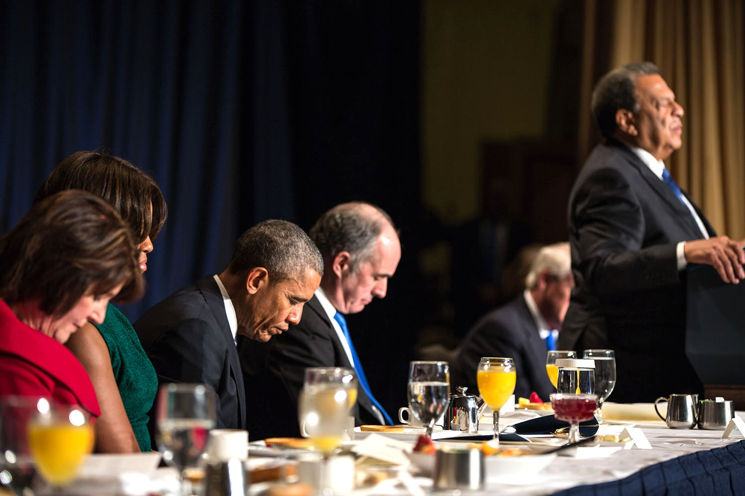 The President and First Lady Michelle Obama join former Atlanta Mayor Andrew Young in the closing prayer during the National Prayer Breakfast