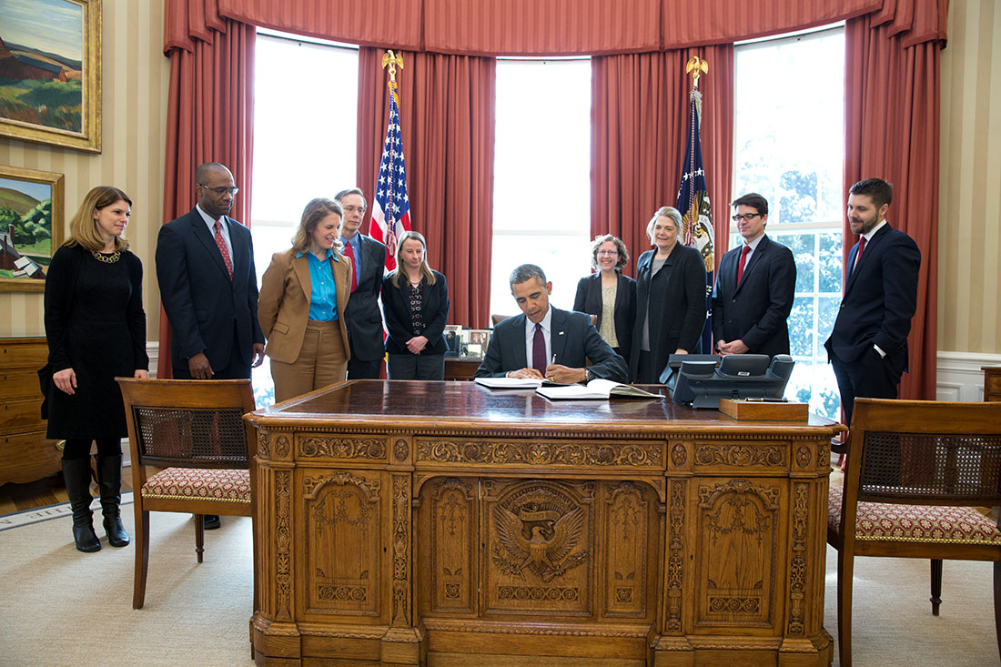 President Barack Obama signs copies of the FY 2015 Budget as Sylvia Mathews Burwell, Director, Office of Management and Budget, and OMB staff look on in the Oval Offic