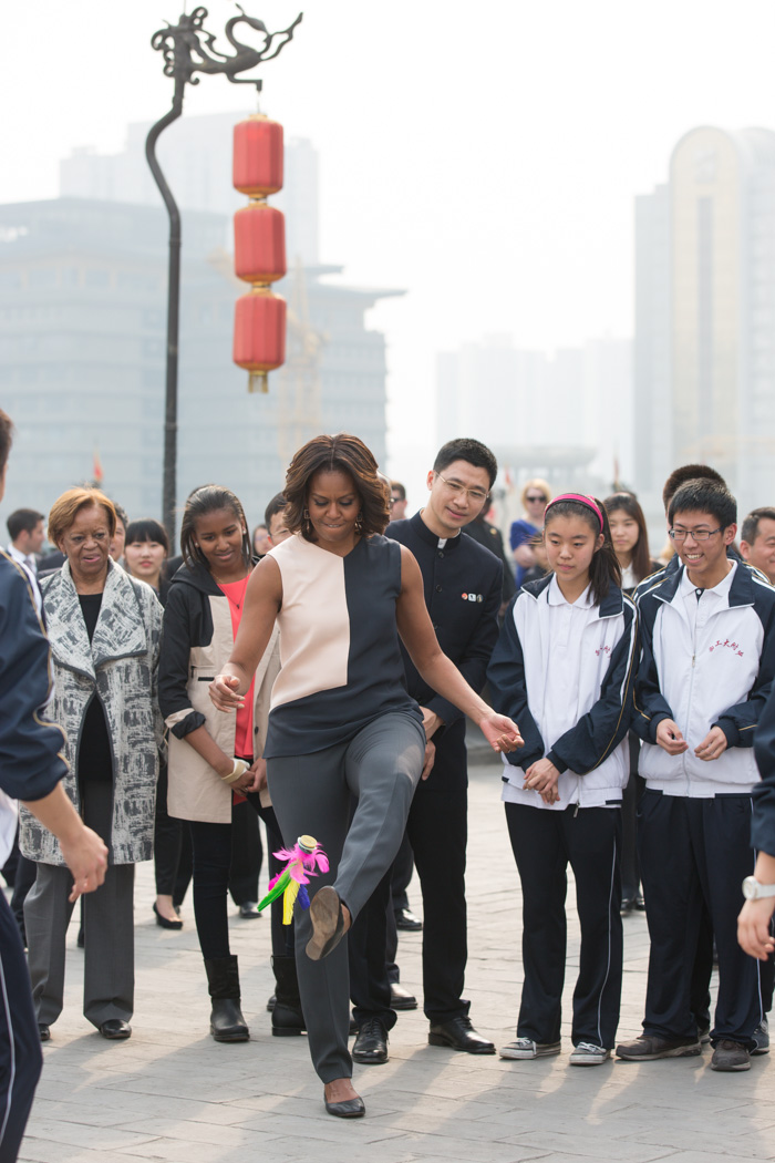 First Lady Michelle Obama participates in a hacky sack demonstration with the help of student instruction during her visit to the Xi'an City Wall with Sasha, Malia and Marian Robinson in Xi'an, China