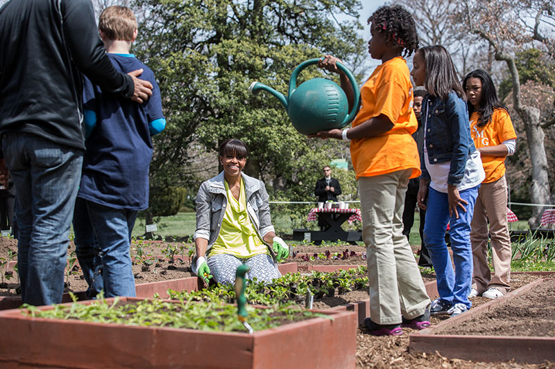 First Lady Michelle Obama and students participate in the Spring White House Kitchen Garden planting