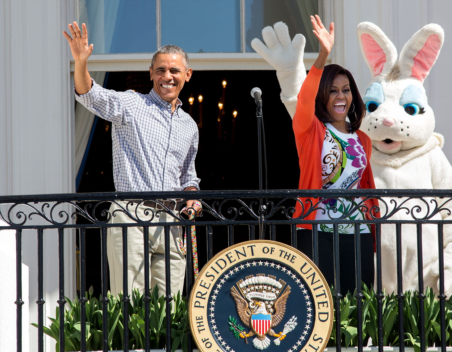 President Barack Obama and First Lady Michelle Obama and the Easter Bunny wave from the Blue Room Balcony